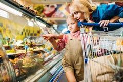belle madre e figlia con il carrello di acquisto che sceglie alimento mentre comperando immagine stock libera da diritti