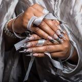 Belle main de la fille avec la greffe de peau foncée des clous acryliques avec fotmoy peu commun de clou Images libres de droits