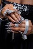Belle main de la fille avec la greffe de peau foncée des clous acryliques avec fotmoy peu commun de clou Images stock