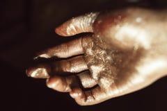 Belle main en peinture d'or sur le fond noir Photo libre de droits