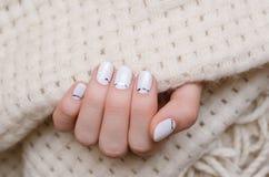 Belle main femelle avec la conception blanche de clou Photographie stock libre de droits