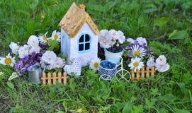 Belle maison avec les wildflowers, la barrière et la boîte d'arrosage Images stock