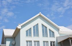 Belle maison moderne avec les murs blancs, les tuiles de toit blanches et les grandes fenêtres à la maison panoramiques de grenie photographie stock