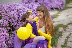 Belle maman blonde de mère avec sa fille de sourire mignonne de fille portant les vêtements colorés appréciant le temps ensemble  Photo stock