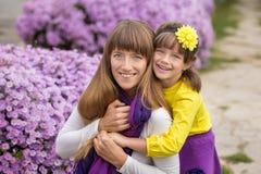 Belle maman blonde de mère avec sa fille de sourire mignonne de fille portant les vêtements colorés appréciant le temps ensemble  Photographie stock