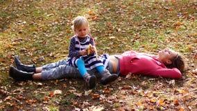 Belle maman et enfant mignon se trouvant sur l'herbe en parc d'automne La fille s'assied sur la maman et mange la banane, regards banque de vidéos