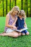 Belle maman et fille lisant dehors Images libres de droits
