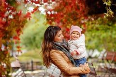 Belle maman très avec du charme de brune dans une veste brune tenant a Photos stock
