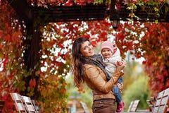 Belle maman très avec du charme de brune dans une veste brune tenant a Photo libre de droits