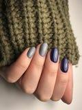 Belle mani con le unghie del manicure in manica khitted del maglione Immagini Stock