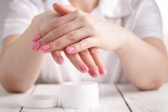 Belle mani della donna con crema immagini stock