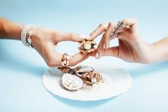 Belle mani della donna con il piatto rosa della tenuta del manicure con le perle e le conchiglie, concetto di lusso dei gioielli Fotografia Stock