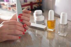 Belle mani e unghie della donna con il manicure perfetto Concetto di trattamento di bellezza Strumenti del manicure Fotografie Stock