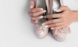 Belle mani femminili con le unghie lunghe e manicure francese sulle scarpe di nozze Fotografia Stock