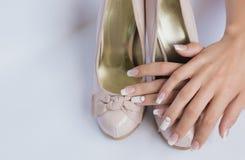 Belle mani femminili con le unghie lunghe e manicure francese sulle scarpe di nozze con un arco su un fondo bianco Fotografia Stock Libera da Diritti