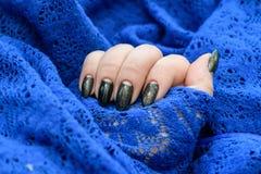 Belle manucure d'hiver La laque noire avec le lustre et les modèles blancs de la neige et givrent le fond bleu est également images stock