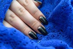 Belle manucure d'hiver La laque noire avec le lustre et les modèles blancs de la neige et givrent le fond bleu est également photo libre de droits