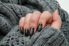 Belle manucure d'hiver La laque noire avec le lustre et les modèles blancs de la neige et givrent le fond gris est également photo stock