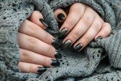 Belle manucure d'hiver La laque noire avec le lustre et les modèles blancs de la neige et givrent le fond gris est également photo libre de droits