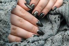 Belle manucure d'hiver La laque noire avec le lustre et les modèles blancs de la neige et givrent le fond gris est également photos libres de droits