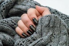 Belle manucure d'hiver La laque noire avec le lustre et les modèles blancs de la neige et givrent le fond gris est également photographie stock libre de droits