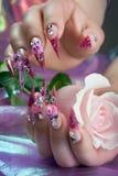 Belle manucure des mains avec une rose Photo libre de droits