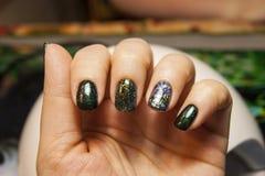 Belle manucure verte, vernis à ongles sur des ongles de différentes nuances de vert, avec un léger éclat et un grand miroitement photographie stock libre de droits