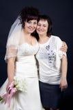 Belle mariée avec sa soeur sur un backgro noir Images stock