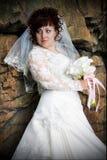 Belle mariée avec un bouquet, parmi les murs rugueux Images libres de droits