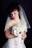 Belle mariée avec un bouquet un fond noir Photos stock