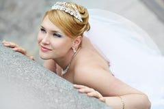 Belle mariée dans la robe de mariage près du parapet Images stock