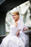 Belle mariée dans une robe de mariage près de parapet Photos stock