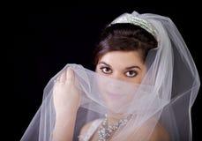 Belle mariée regardant au-dessus de son voile contre Blac Image stock