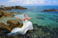 Belle mariée s'asseyant au-dessus du cristal - mer claire Image libre de droits