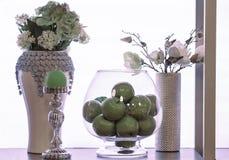Belle mele brillanti in vaso di vetro trasparente e due vasi con i fiori bianchi contro una parete d'ardore bianca Immagini Stock Libere da Diritti