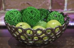 Belle mele brillanti verdi in un vaso di vetro su un fondo rosso della parete Fotografia Stock