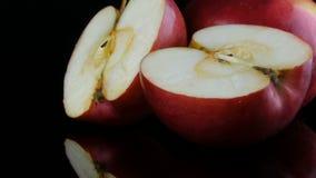 Belle mele rosse succose mature sulla superficie dello specchio e sui precedenti neri Frutta, alimento sano, dieta video d archivio