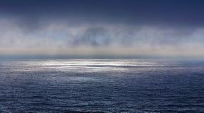 Belle mer avec les nuages profonds foncés dans le coucher du soleil Image stock