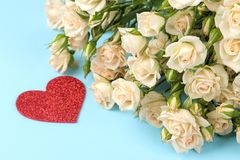 Belle mini rose con un cuore rosso su un fondo blu luminoso feste Giorno del `s del biglietto di S Primo piano fotografia stock