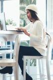 Belle mise en réseau de fille dans un café avec l'ordinateur portable Photos libres de droits
