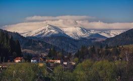 Belle montagne innevate contro il cielo blu Paesino di montagna nella priorità alta Immagine Stock