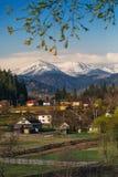 Belle montagne innevate contro il cielo blu Paesino di montagna nella priorità alta Fotografia Stock