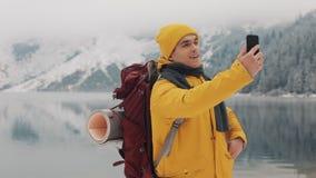Belle montagne nell'orario invernale L'uomo con la barba, vestiti gialli d'uso dell'inverno prende il selfie contro lo sfondo di stock footage