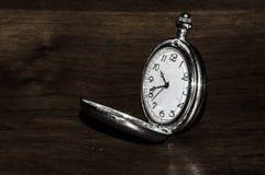 Belle montre de poche en métal sur un fond en bois photographie stock