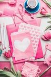 Belle moquerie de rose avec les tulipes, le paquet de papier avec des coeurs, le stylo de marqueur, les étiquettes et la tasse de Photos libres de droits