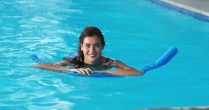 Belle natation de femme avec le tube gonflable dans la piscine banque de vidéos