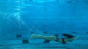 Belle natation de jeune femme sous l'eau dans la piscine banque de vidéos