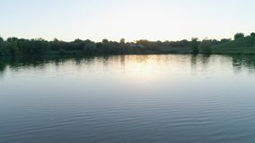Belle nature, lac propre parmi les arbres verts contre le ciel à la postluminescence banque de vidéos