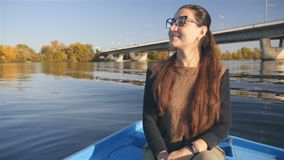 Belle navigation de fille sur la rivière dans un bateau Un sourire joyeux Beau paysage Jour d'été ensoleillé Voyage sur banque de vidéos
