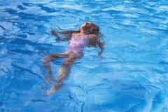 Belle nuotate nello stagno, bambina sveglia della bambina in stagno nel giorno soleggiato immagine stock libera da diritti